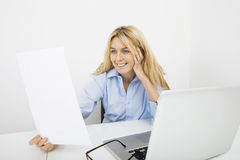 Happy businesswoman reading document in office Stock Photo
