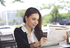 Happy businesswoman reading newspaper and smile Stock Image