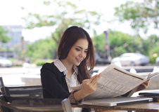 Happy businesswoman reading newspaper and smile Royalty Free Stock Image