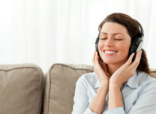 Happy businesswoman relaxing with music. In the living-room at home Stock Images