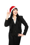Happy businesswoman in santa hat pointing up Royalty Free Stock Photography