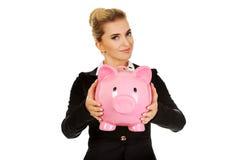 Happy businesswoman saving money in piggybank Stock Photos