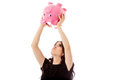 Happy businesswoman saving money in piggybank. Isolated on white Royalty Free Stock Photography