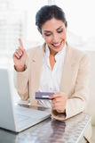 Happy businesswoman shopping online with laptop and pointing Stock Photo