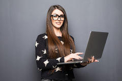 Happy businesswoman showing blank laptop screen over gray background. Royalty Free Stock Photography
