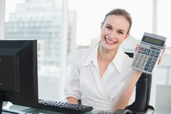 Happy businesswoman showing calculator sitting at desk Stock Image