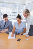 Happy businesswoman showing colleagues something on her notepad Stock Photo