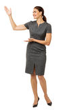 Happy Businesswoman Showing An Imaginary Product. Full length of happy businesswoman showing an imaginary product isolated over white background. Vertical shot Stock Photos