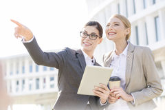 Happy businesswoman showing something to colleague while using tablet PC Royalty Free Stock Photos
