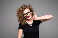 Happy businesswoman showing thumb up over gray background. Looking at camera stock images