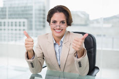 Happy businesswoman showing thumbs up at her desk Stock Image