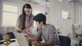 Happy businesswoman shows info on tablet to Japanese young colleague. Multiethnic people work in modern light office 4K stock video