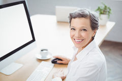 Happy businesswoman sitting at computer desk Stock Photography