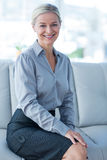Happy businesswoman sitting on couch Stock Images