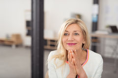 Happy businesswoman sitting daydreaming. Happy successful blond businesswoman sitting daydreaming in the office looking into the distance with a wide smile of Royalty Free Stock Photos