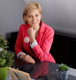 Happy businesswoman sitting at desk Royalty Free Stock Images