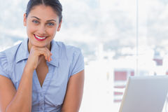 Happy businesswoman sitting at her desk Stock Photography