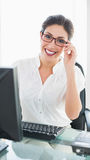 Happy businesswoman sitting at her desk Stock Image