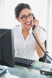 Happy businesswoman sitting at her desk talking on the phone Royalty Free Stock Photo