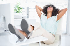 Happy businesswoman sitting with her feet up Royalty Free Stock Images