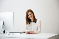 Happy businesswoman sitting at her workplace in office Stock Image