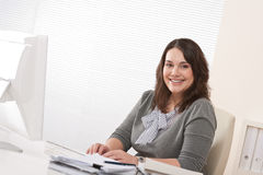 Happy businesswoman sitting at office desk Stock Images