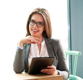 Happy businesswoman sitting  in office with laptop on white Stock Photo