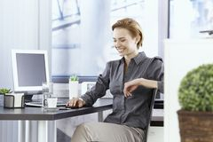 Happy businesswoman sitting in office Stock Photography