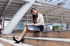 Happy businesswoman sitting on sidewalk. Royalty Free Stock Photography