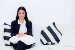 Happy businesswoman sitting on the sofa looking at camera in the office. The happy businesswoman sitting on the sofa looking at camera in the office Stock Photo