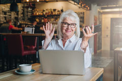 Happy businesswoman sitting at table in front of laptop, holding hands up and smiling, working, learning. In hands of woman in a smartphone. Good news Royalty Free Stock Images