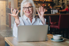 Happy businesswoman sitting at table in front of laptop, holding hands up and smiling, working, learning Royalty Free Stock Photography
