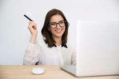 Happy businesswoman sitting at the table with laptop Stock Photos
