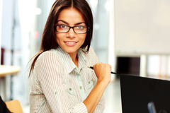 Happy businesswoman sitting at the table Stock Images