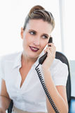 Happy businesswoman sitting talking on the phone Stock Photography