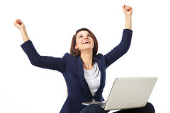 Young businesswoman celebrating a success working with laptop Stock Photo