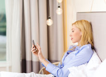 Happy businesswoman with smartphone in hotel room Stock Photography