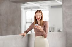 Happy businesswoman with smartphone at office royalty free stock image