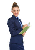 Happy businesswoman smiling at camera, holding notebook and pen Stock Photo