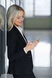 Happy businesswoman smiling and using smartphone in office Royalty Free Stock Images