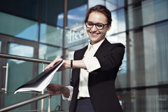 Happy businesswoman smilling and checking watch. Royalty Free Stock Images