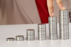 Happy businesswoman with stack of coins and holding rupee notes Royalty Free Stock Image