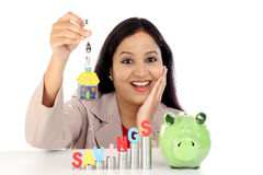 Happy businesswoman with stack of coins and piggy bank Royalty Free Stock Photography