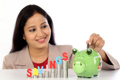 Happy businesswoman with stack of coins and piggy bank Royalty Free Stock Photos