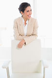 Happy businesswoman standing behind her chair Stock Photography