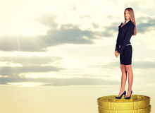 Happy businesswoman standing on coins stack Royalty Free Stock Images