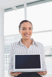 Happy businesswoman standing showing laptop screen Royalty Free Stock Image