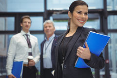 Happy businesswoman standing with spiral book. In office Royalty Free Stock Image