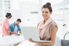 Happy businesswoman standing and using laptop Stock Photography