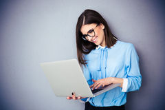 Happy businesswoman standing and using laptop. Over gray background. Wearing in blue shirt and glasses Royalty Free Stock Image